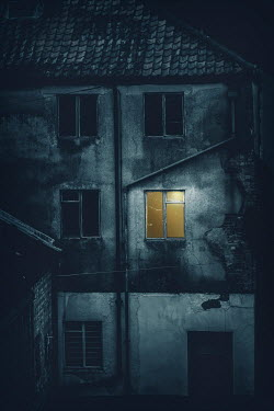 Nic Skerten LIGHT IN WINDOW OF WEATHERED BUILDING AT NIGHT Houses