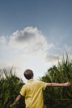 Yolande de Kort BOY TOUCHING TALL PLANTS IN COUNTRYSIDE