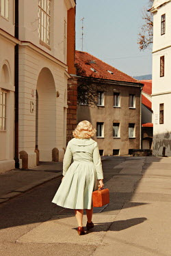 Jasenka Arbanas BLONDE RETRO WOMAN CARRYING SUITCASE IN TOWN