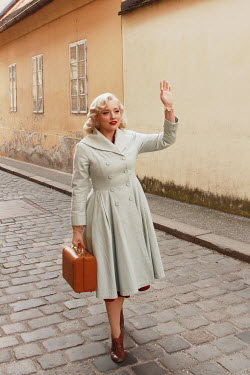 Jasenka Arbanas BLONDE WOMAN WAVING AND CARRYING CASE IN STREET