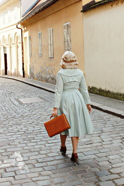 Jasenka Arbanas BLONDE WOMAN WALKING AND CARRYING CASE IN STREET