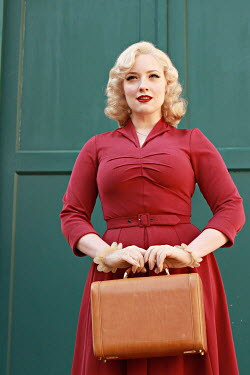 Jasenka Arbanas BLONDE RETRO WOMAN CARRYING SUITCASE OUTDOORS