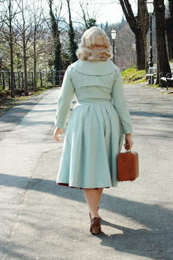 Jasenka Arbanas BLONDE WOMAN WALKING AND CARRYING CASE IN ROAD