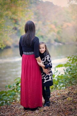 Susan Fox MOTHER HUGGING DAUGHTER BY RIVER IN COUNTRYSIDE