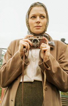 CollaborationJS WOMAN IN HEADSCARF HOLDING CAMERA