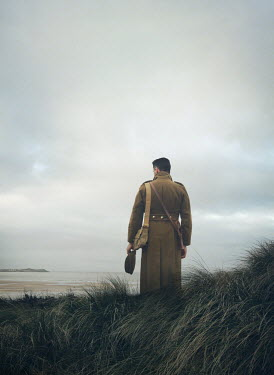 Mark Owen SOLDIER STANDING IN DUNES WATCHING SEA