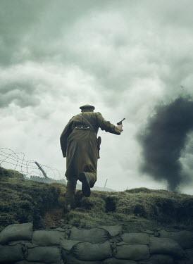 Mark Owen SOLDIER WITH GUN RUNNING IN FIELD WITH EXPLOSION
