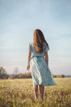 Joanna Czogala GIRL IN FLORAL DRESS STANDING IN COUNTRYSIDE