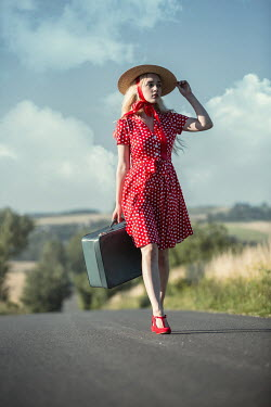 Magdalena Russocka young woman with straw hat and suitcase walking on country road