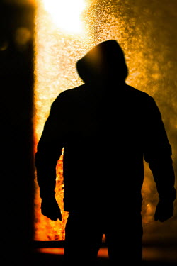 Magdalena Russocka silhouette of man in hoodie standing by door with light