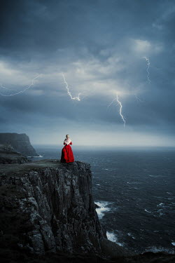 Magdalena Russocka historical woman standing on cliff during storm