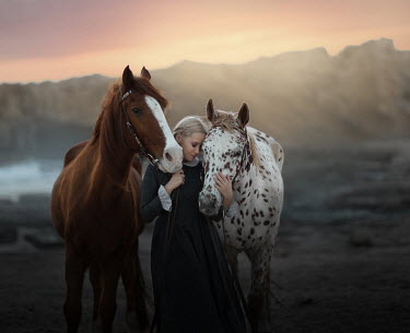 Sveta Butko WOMAN WITH TWO HORSES OUTDOORS AT SUNSET