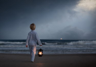 Sveta Butko LITTLE BOY CARRYING LANTERN ON BEACH AT DUSK