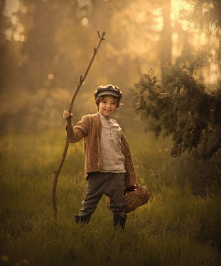 Sveta Butko LITTLE BOY HOLDING BRANCH AND BASKET IN COUNTRYSIDE
