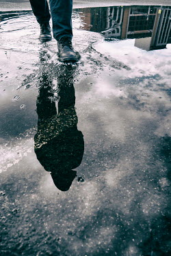 Tim Robinson REFLECTION OF MAN WALKING IN PUDDLE