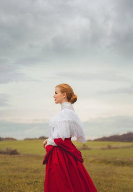 Joanna Czogala HISTORICAL WOMAN WITH RED HAIR STANDING IN FIELD