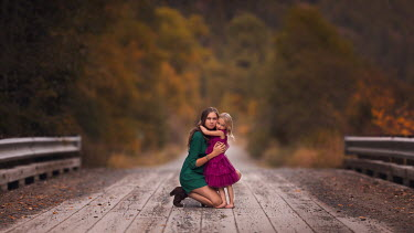 Lisa Holloway WOMAN HUGGING LITTLE GIRL ON BRIDGE