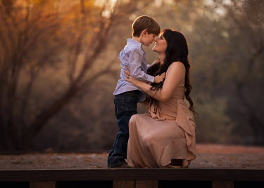 Lisa Holloway WOMAN HUGGING LITTLE BOY IN AUTUMN COUNTRYSIDE