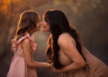 Lisa Holloway SMILING MOTHER AND DAUGHTER HOLDING HANDS OUTDOORS