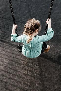 Matilda Delves LITTLE GIRL IN DRESS SITTING ON SWING