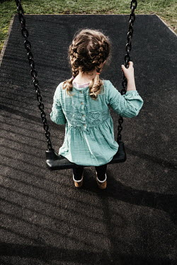 Matilda Delves LITTLE GIRL IN DRESS SITTING ON SWING