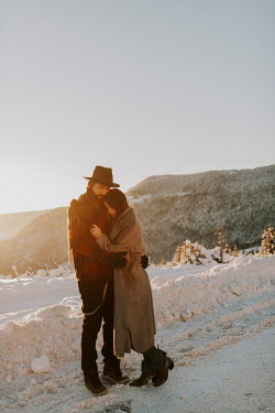 Muna Nazak COUPLE EMBRACING IN SNOWY COUNTRYSIDE