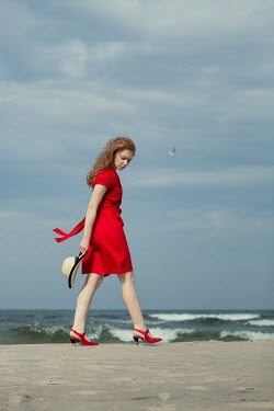 Magdalena Russocka woman in red dress holding hat walking on beach