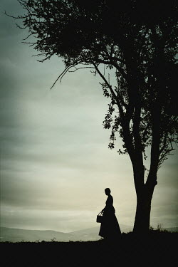 Magdalena Russocka silhouette of historical woman standing by tree