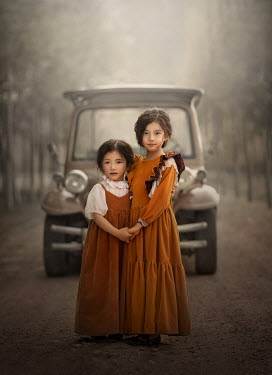 Sveta Butko TWO LITTLE GIRLS HOLDING HANDS BY CAR ON ROAD