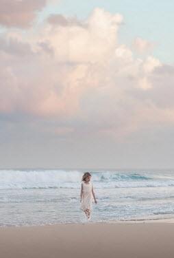 Sveta Butko LITTLE GIRL PADDLING ON SANDY BEACH