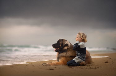 Sveta Butko LITTLE BOY SITTING ON SANDY BEACH WITH DOG