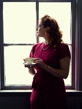Elisabeth Ansley RETRO WOMAN WITH TEACUP WAITING BY WINDOW