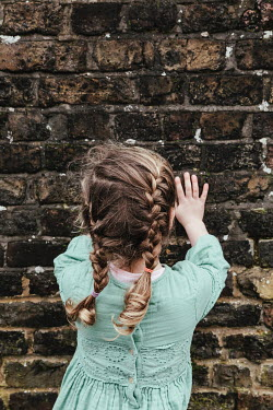 Matilda Delves LITTLE GIRL WITH PLAITS TOUCHING BRICK WALL