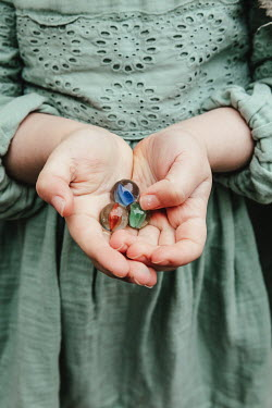 Matilda Delves HANDS OF LITTLE GIRL HOLDING MARBLES