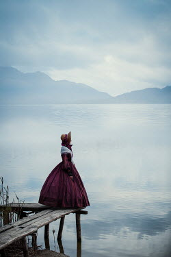 Magdalena Russocka historical woman standing on pier by lake