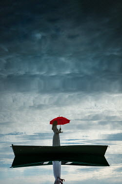 Magdalena Russocka woman with umbrella standing in boat on lake
