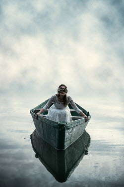 Magdalena Russocka blindfolded woman sitting in boat on lake