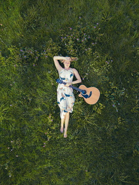 Mary Wethey WOMAN WITH GUITAR LYING IN FIELD