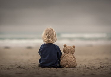 Sveta Butko LITTLE BLONDE CHILD SITTING ON BEACH WITH TEDDY