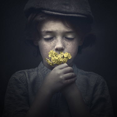Sveta Butko LITTLE BOY IN CAP SMELLING YELLOW FLOWERS