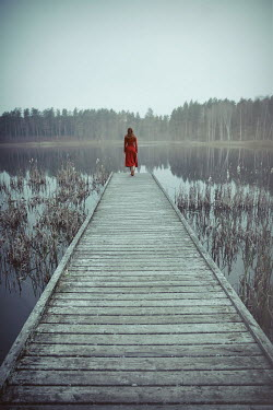 Natasza Fiedotjew young woman in red dress walking on wooden jetty at lake