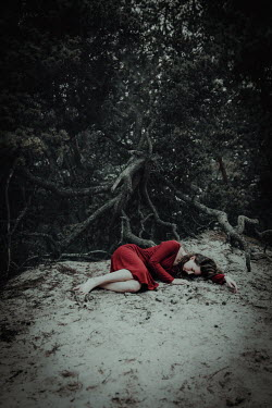 Natasza Fiedotjew woman in red dress lying on sand under pine tree