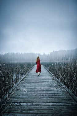 Natasza Fiedotjew teenage girl in red dress running on wooden jetty at lake