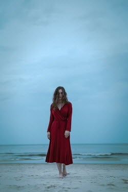 Natasza Fiedotjew teenage girl in red dress standing on beach in dusk