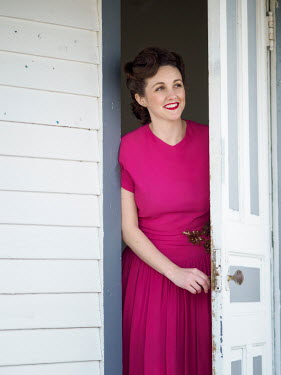 Elisabeth Ansley SMILING 1940S WOMAN IN DRESS OPENING DOOR