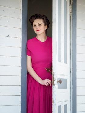 Elisabeth Ansley 1940S WOMAN IN PINK DRESS OPENING DOOR