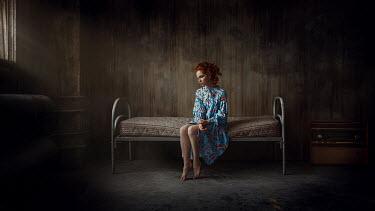 Georgy Chernyadyev WOMAN WITH RED HAIR SITTING IN BLEAK BEDROOM