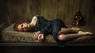 Georgy Chernyadyev WOMAN WITH RED HAIR LYING ON MATTRESS WITH CLOCK