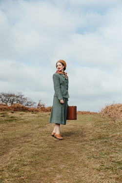 Matilda Delves 1940S WOMAN CARRYING SUITCASE IN COUNTRYSIDE
