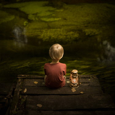 Sveta Butko BLONDE LITTLE BOY WITH LANTERN SITTING ON JETTY